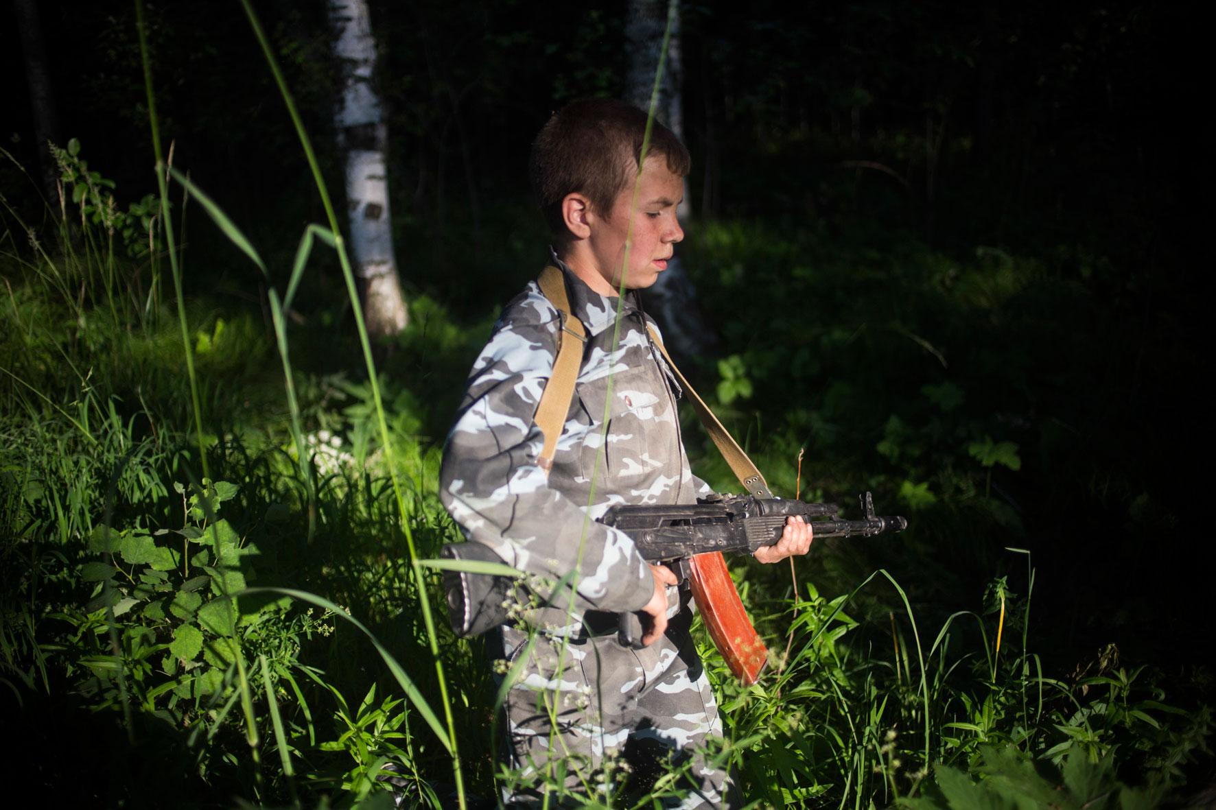Während des »Marsh Brosok«, einem Kriegspiel zum Ende der Lagerzeit, geht ein Junge mit einer echten AK-47 der Sonne entgegen.