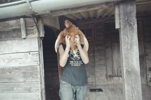 Felix, 15, auf dem Hof seiner Pflegefamilie in Mecklenburg-Vorpommern. Er hält ein Huhn, um es fliegen zu lassen.