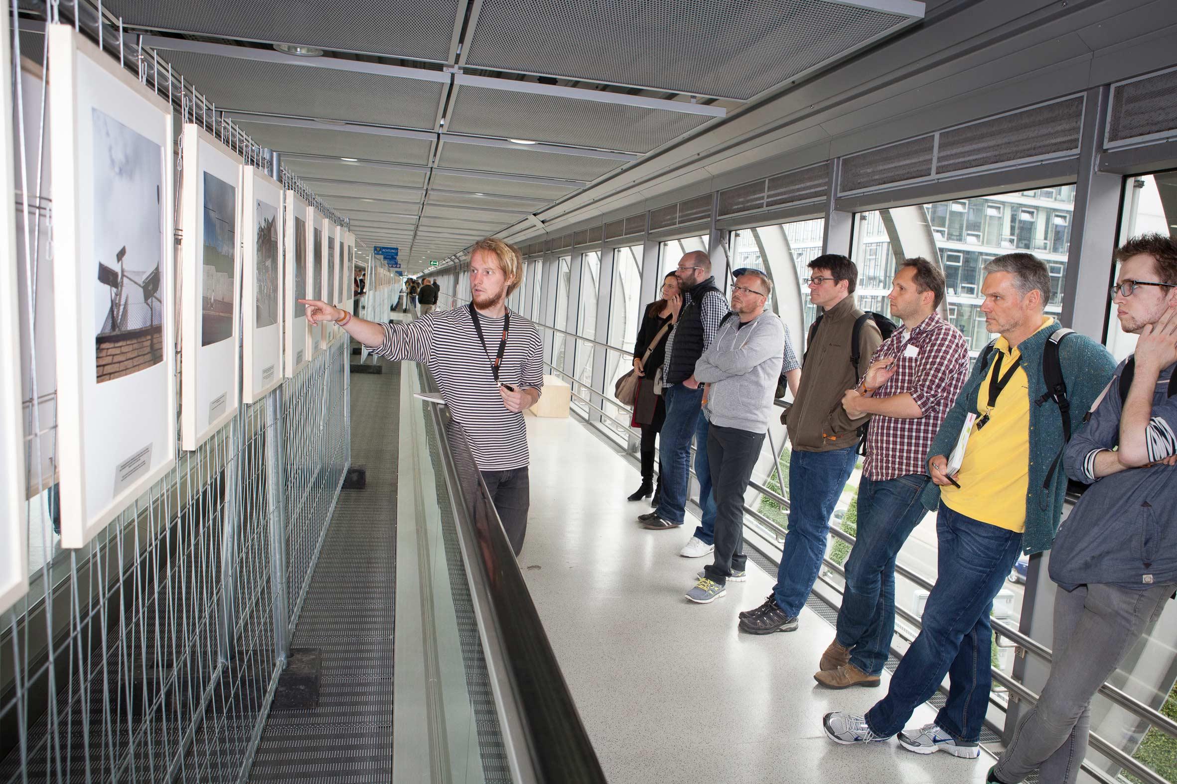 Konrad Lippert zeigt den interessierten Besuchern seine Ausstellung »They call it trouble«.