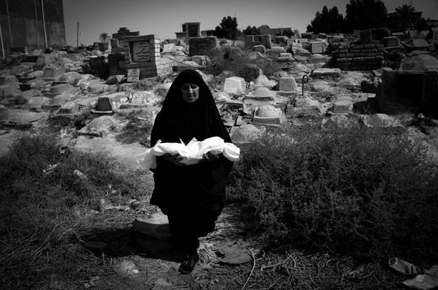 Eine alte Frau trägt den in Leinen eingewickelten Leichnam eines Kindes auf dem Kinderfriedhof in Basrah zur Grabstätte. Irak 2012.