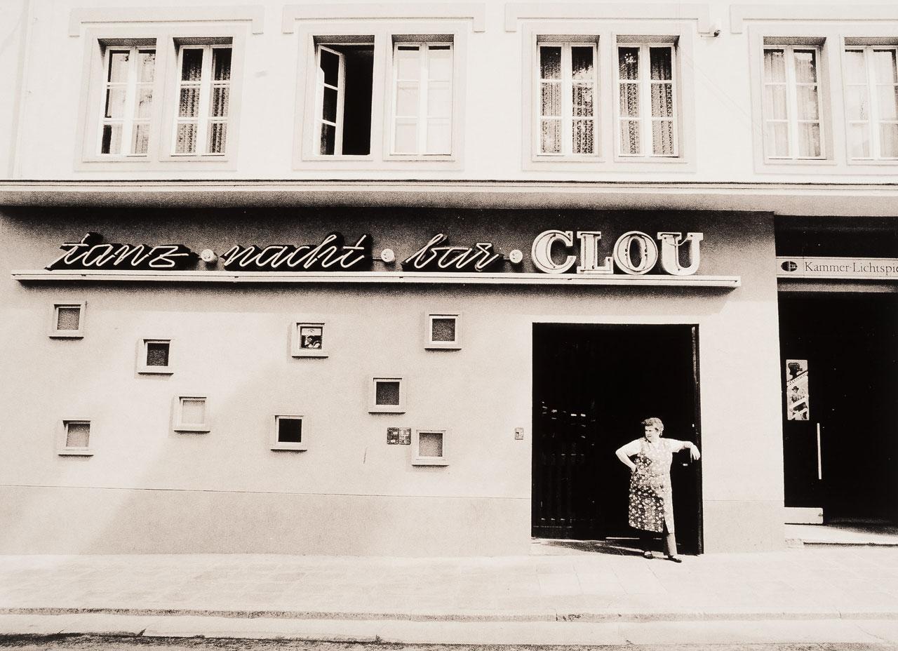 Am Morgen. Putzfrau macht im Eingang einer Nachtbar ein kurze Pause, Cottbus, Mai 1990.