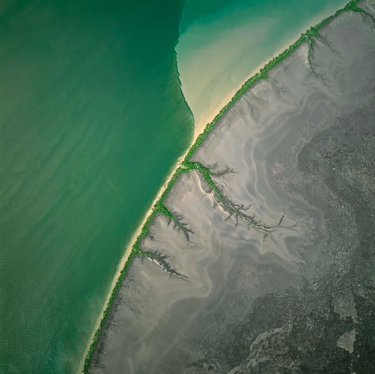 Mangroven am Ufer und Algen im Wasser bringen verschiedene Grüntöne in die kahle Schwemmebene des Alligator-River. Im Fluss grenzt von Algen dunkelgrün gefärbtes Wasser an das mit Schwebstoffen beladene, helle Wasser, das Nebenarme ins Flussbett spülen. Die unterschiedliche Dichte verhindert, dass sie sich sofort vermischen. Alligator River, Australien.