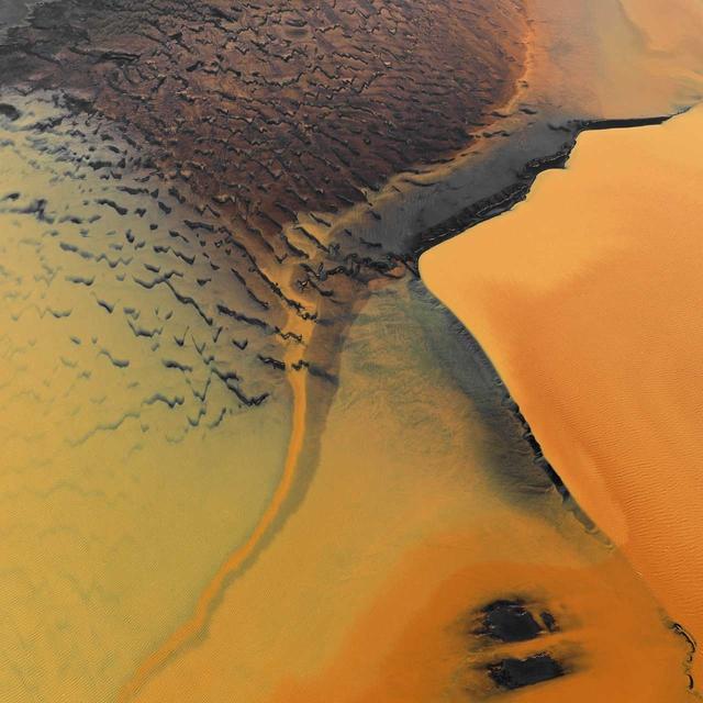Auf den großen Ebenen aus dunklem Vulkansand an der Südküste Islands findet man solche unwirklich anmutenden intensiv orange gefärbten Wasserlandschaften. Sie entstehen überall dort, wo sich eisenschüssiges Moorwasser kurz vor seiner Mündung ins Meer flächig ausbreiten kann. Landeyjarsander, Island.