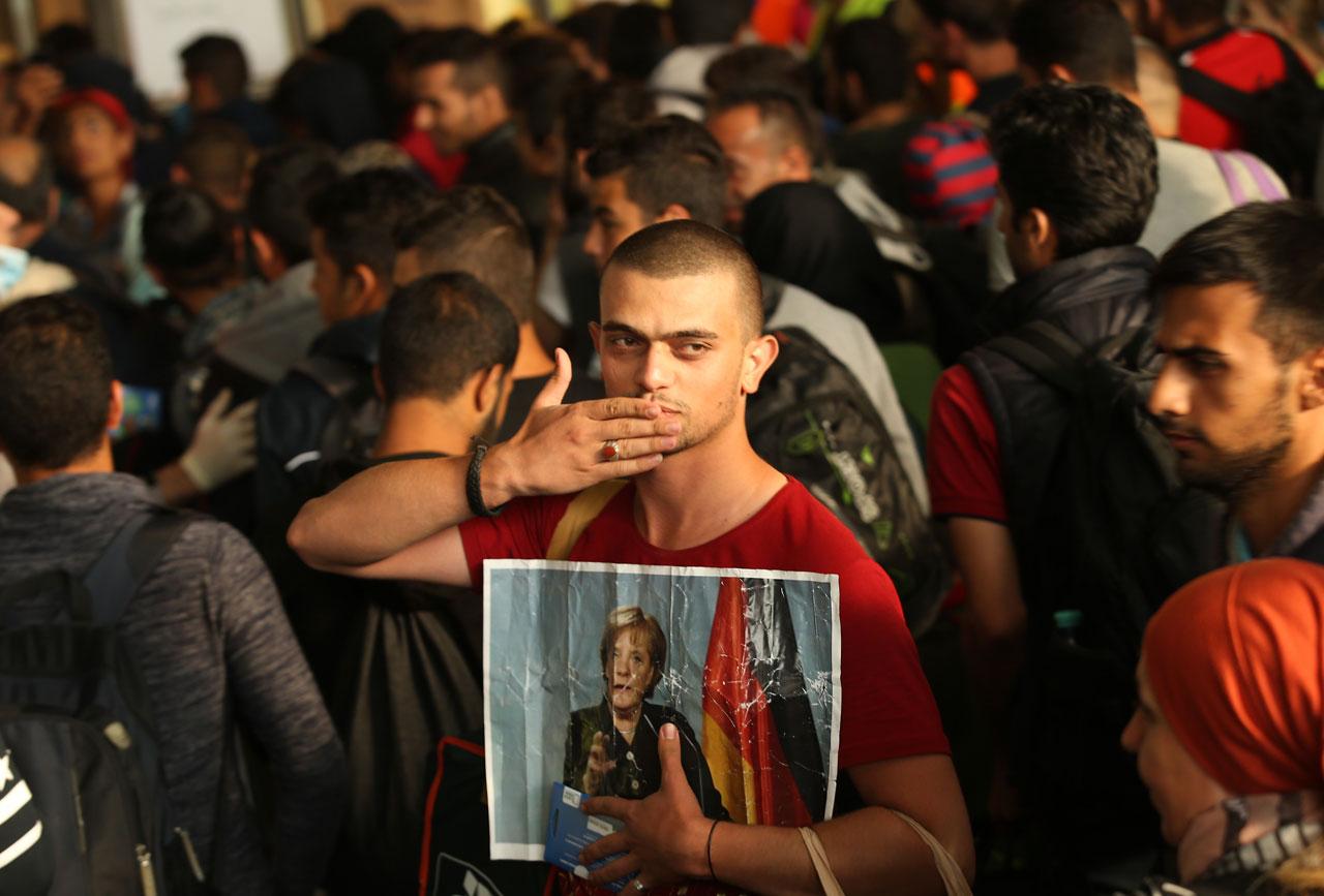 Willkommenskultur. Dankesgeste eines syrischen Flüchtlings bei der Ankunft am Münchner Hauptbahnhof im September 2015. Foto: Sean Gallup