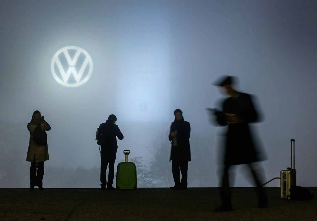 Trübe Aussichten bei VW. Zugreisende am Bahnsteig in Wolfsburg fotografieren das nahezu im Nebel verschwundene Banner der Volkswagen AG mit der Aufschrift: »Wir brauchen Transparenz, Offenheit, Energie und Mut. Vor allem aber brauchen wir Euch.« Foto: Paul Langrock/Zenit
