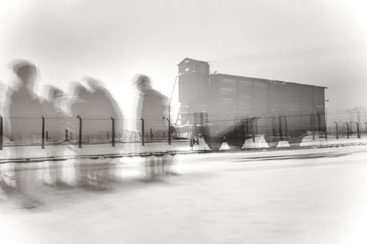 Besuchergruppe vor einem Eisenbahnwaggon in Auschwitz-Birkenau Ende Januar 2015. Durch die Langzeitbelichtung wirkt die Szene wie eingefroren.