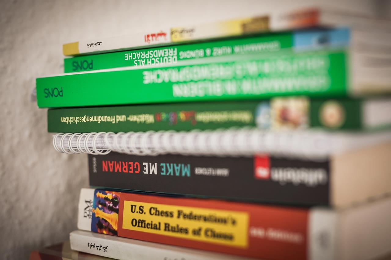 Der Bücherstapel auf dem Familienschreibtisch besteht aus Büchern zum Lernen der deutschen Sprache, Schachbüchern und Integrationsratgebern.