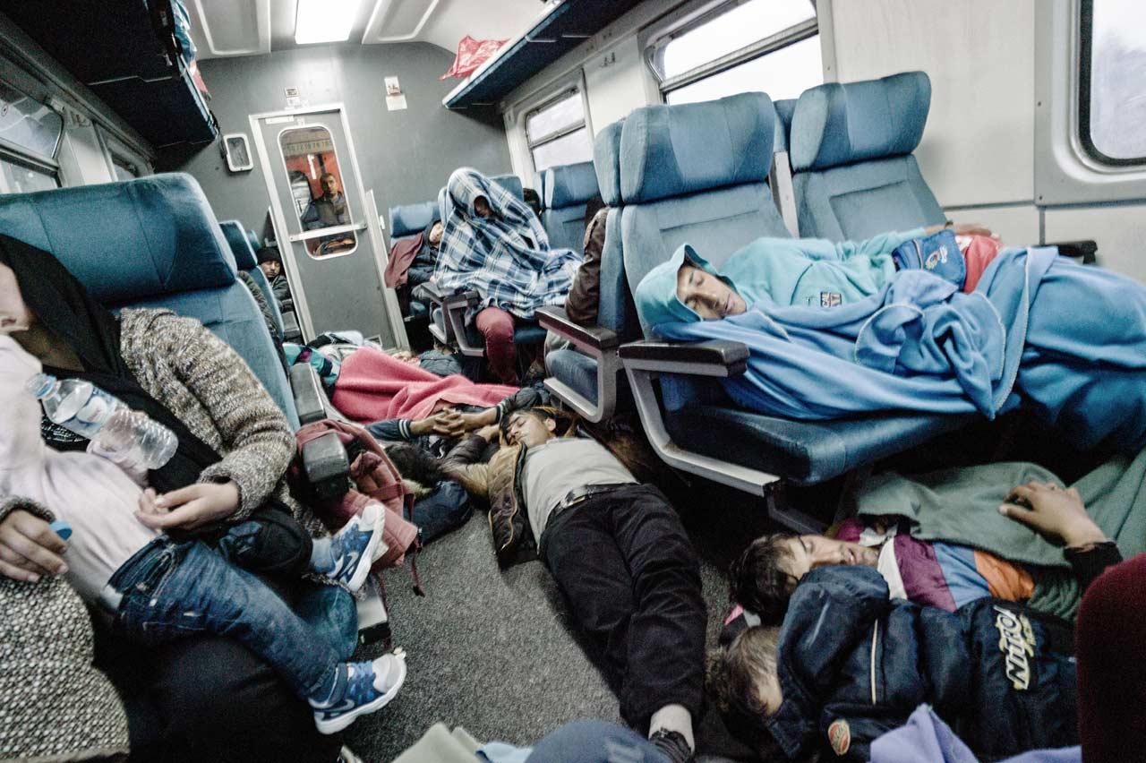 Während der nächtlichen Zugfahrt bis zur kroatischen Grenze versuchen die Flüchtlinge, wenigstens ein bisschen zu schlafen. Foto: Felix Kleymann
