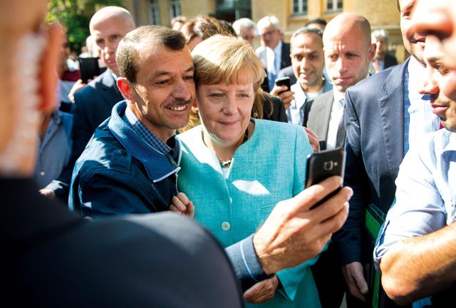 Bundeskanzlerin Angela Merkel lässt sich nach dem Besuch einer Erstaufnahmeeinrichtung für Asylbewerber in Berlin-Spandau für ein Selfie zusammen mit einem Geflüchteten fotografieren.