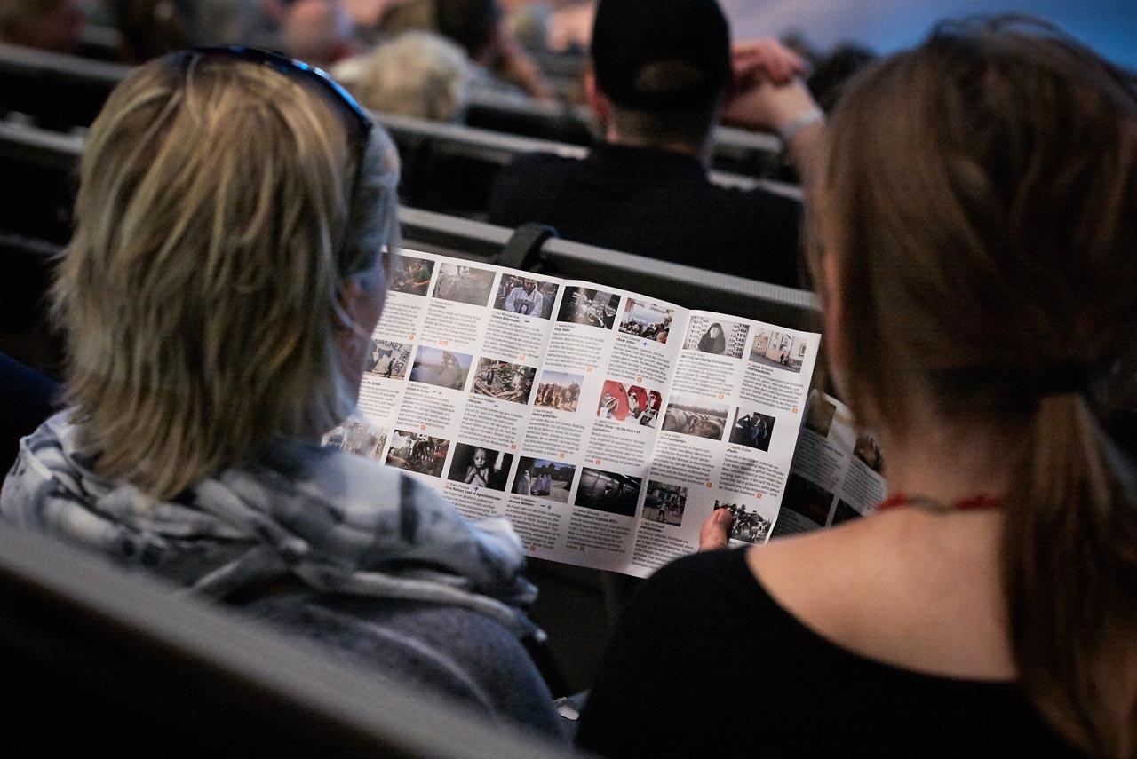 Festivalbesucherinnen beim Studieren des Ausstellungsprogramms.