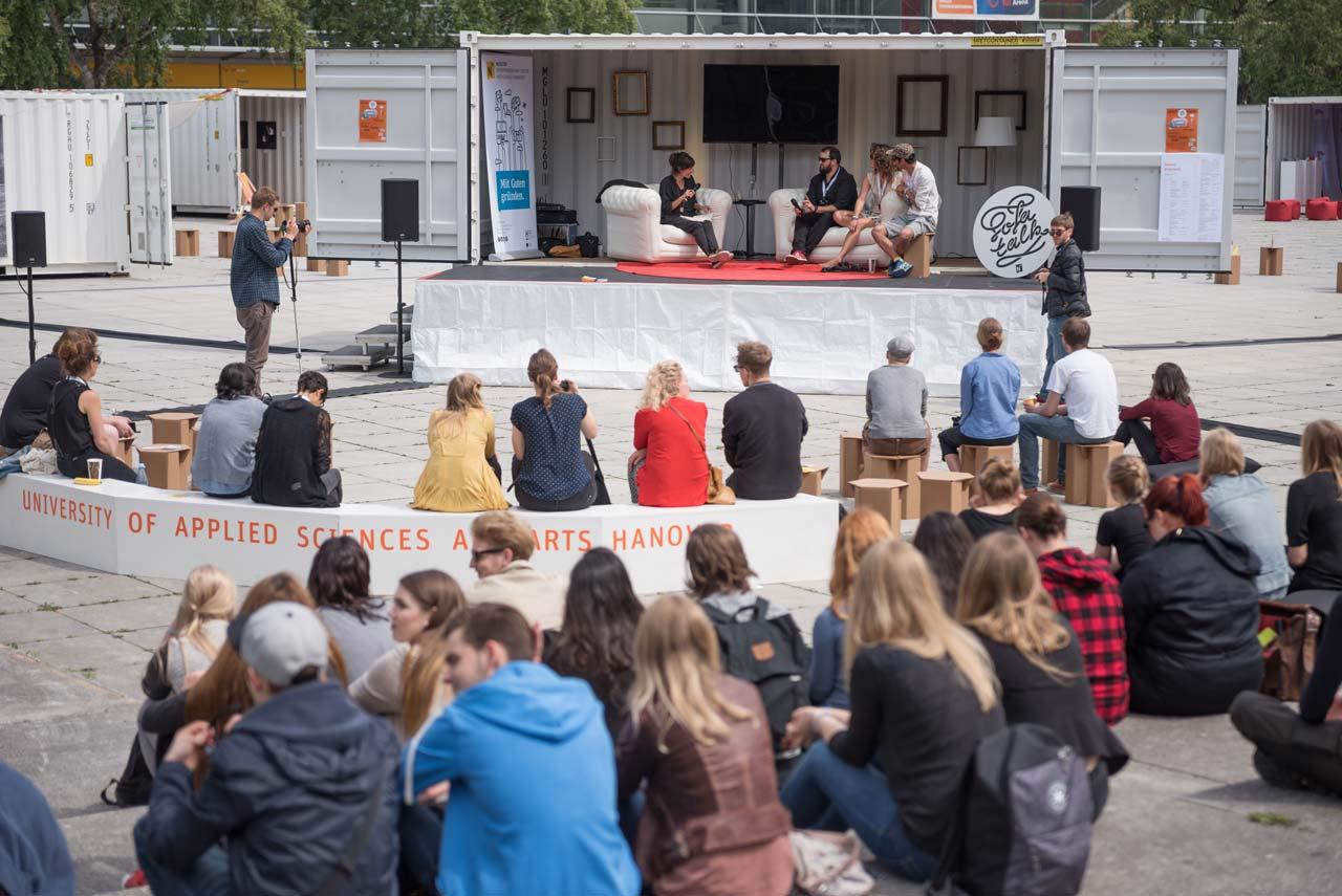 Ein weiterer Treffpunkt war in diesem Jahr das Containerdorf mit der Veranstaltungsbühne: Fabian Fiechter, Alina Emrich und Kien Hoàng Lê vom Cartel Collective beim Sofa Talk mit Dörte Roloff.