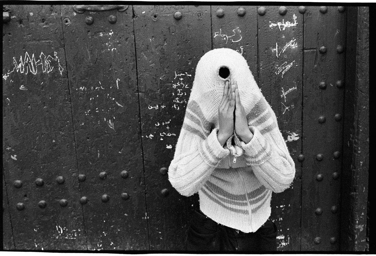 Spontane Straßenszene in den Gassen von Fez in Marokko. Der Junge zieht hitzebedingt seinen Pullover auf eine extravagante Art aus. Nicht sichtbar: der Freund ihm gegenüber lacht sich schlapp bei dieser Handhaltung. Fez, Marokko, 2010.