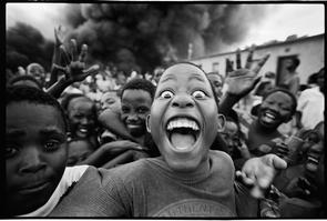 Ein immenser Brand von Autoreifen, wahrscheinlich ausgelöst durch Jugendliche. Voller Energie rast eine Gruppe von Kindern lachend auf den Fotografen zu. Erik Hinz macht in 5 Sekunden manuell 15 Bilder – dann ist die Situation auch schon wieder vorbei. Community Kanyamazane, Region Mpumalanga, Südafrika 1998.