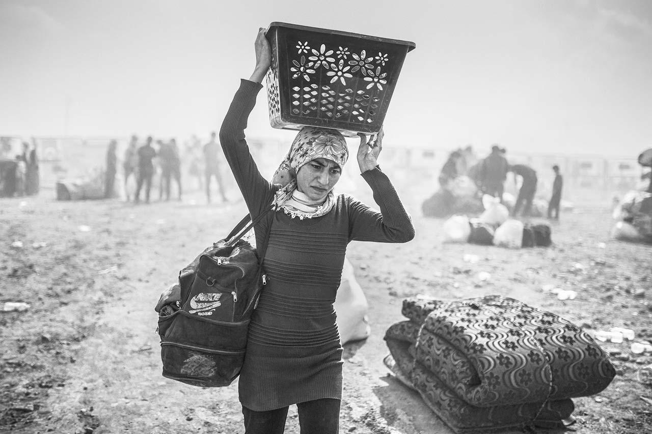 Eine geflüchtete syrische Kurdin überquert mit dem wenigen, was sie in der Eile des Aufbruchs retten konnte, die Grenze zur Türkei bei Suruc, 27. September 2014.