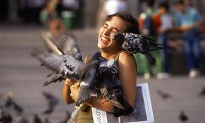Ekstase. Touristin mit Tauben auf dem Mailänder Domplatz.