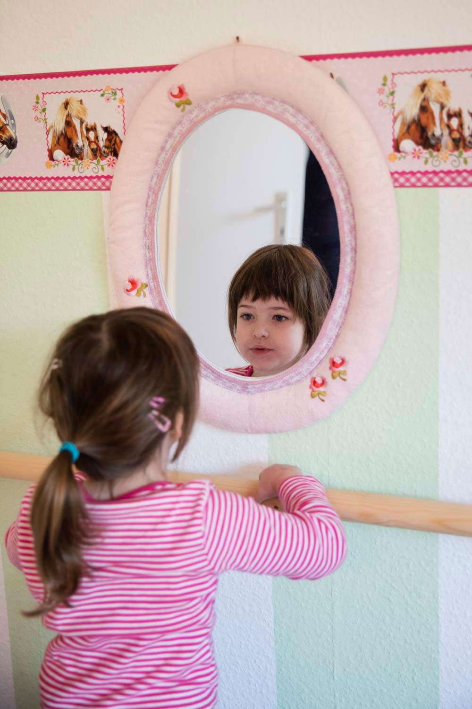 Klara (5) schaut sich im Spiegel in ihrem Kinderzimmer an. Sie leidet an der seltenen Krankheit Neuronale Ceroid-Lipofuszinose, auch Kinderdemenz genannt. Foto: Kathrin Harms