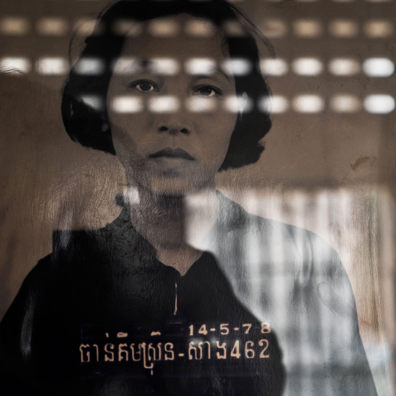 Das Porträt einer Gefangenen, auf einem Stuhl sitzend, der ihren Kopf gerade hielt. Die Frauen wurden manchmal von den Befragten vergewaltigt, obwohl sexueller Missbrauch gegen die Ideologie der Demokratischen Kampuchea (DK) Politik war.