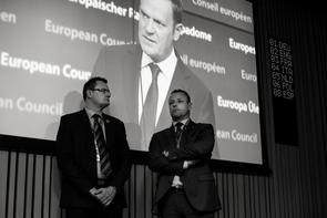 Sicherheitspersonal beim EU-Gipfeltreffen in Brüssel im Dezember 2015 vor einem Monitor, auf dem Donald Tusk, Präsident des europäischen Rates, während einer Ansprache zu sehen ist. Themen des Gipfels waren unter anderem die europäische Flüchtlingspolitik und der »Brexit«.