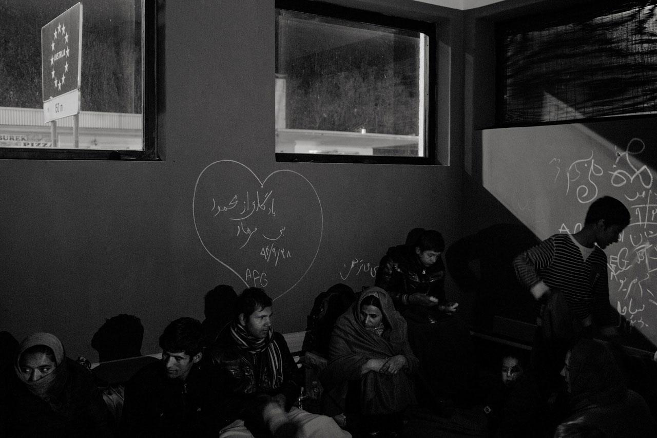Zwei afghanische Familien versuchen, sich in einem verlassenen Gebäude vor der Kälte zu schützen, während sie an der slowenischen Grenze bei Sentilj auf die Weiterreise nach Österreich warten, November 2015. Foto: Kaveh Rostamkhani