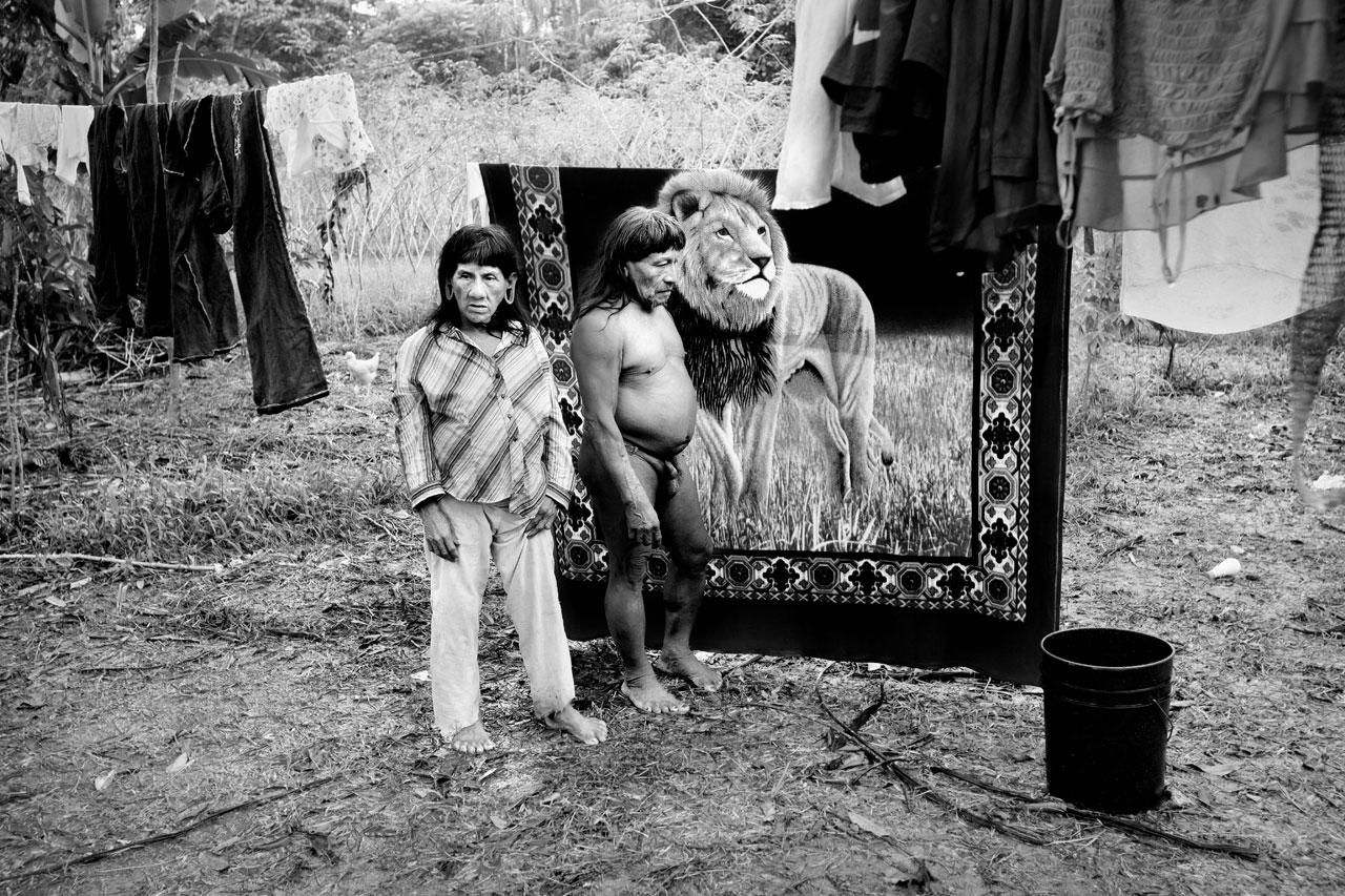 Ecuador, Parque Nacional Yasuní - Zona Intangible, Bameno – pueblo indígena Waorani. A Waorani woman and man in front of a blanket picturing a lion.