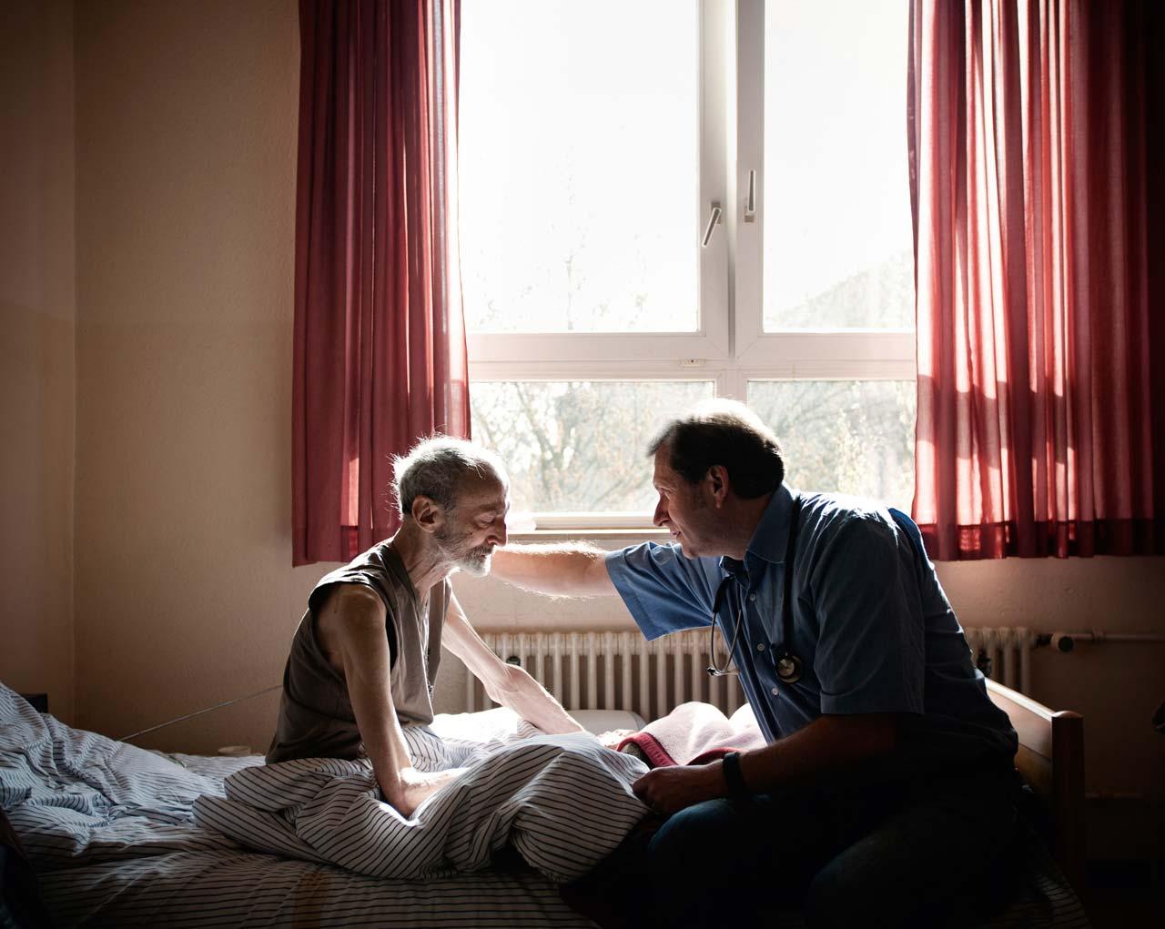 Prof. Dr. Trabert bespricht mit einem Patienten die Verlegung in ein Hospiz.