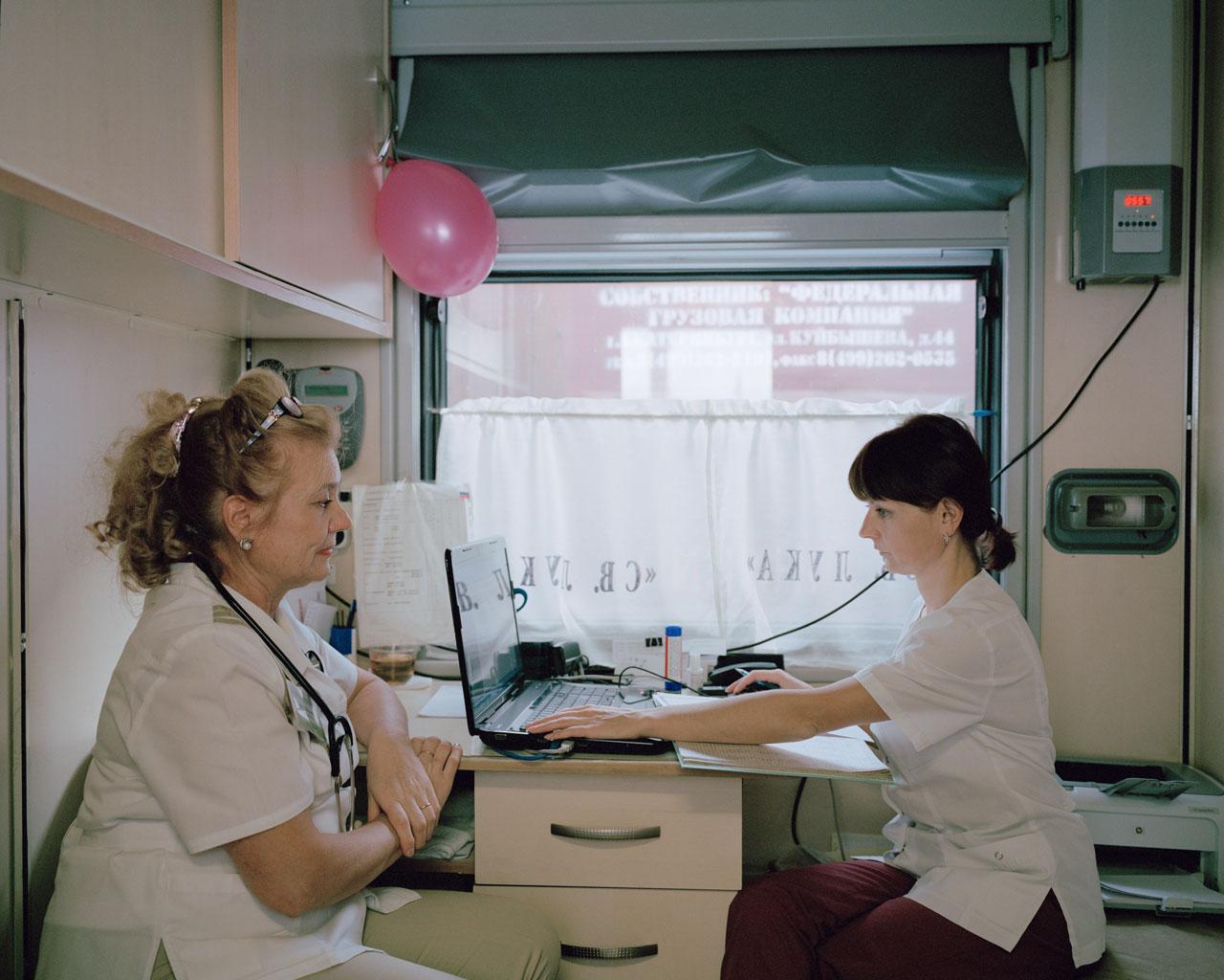 Danilova Lyudmila Mikhailovna (l.) und ihre Assistentin besprechen in einem leeren Zugabteil ihre Diagnosen. Jeden Tag müssen sie sich um ca. 37 Patienten kümmern. Kuragino, Krasnoyarsk Krai, Russland, 2016.