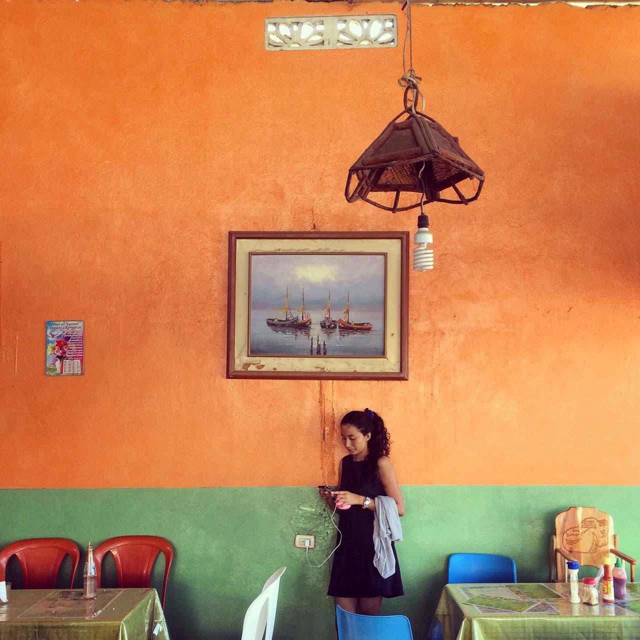 @everydaylatinamerica – Frau beim Aufladen ihres Smartphones in einem Restaurant in Playas, Ecuador, 2017.